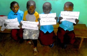 Gahurire Village preschool children show off their school work.