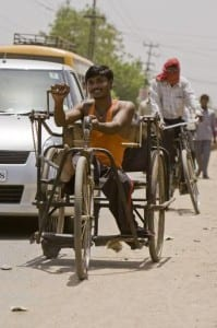 A polio survivor hand peddles his three wheeled bicycle on the street in Mithipur, a small village outside Patna, India. This area is considered a high risk block for the transmission of the polio virus. Nearby, local Rotarians have built a clinic and permanent polio immunization center called Shankar Nath Clinic.