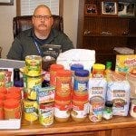 Fulton Rotary President Charlie Anderson sits behind his desk covered with some of the 100 pounds of food donated by the club to the SERVE food pantry. The club also collected $2,170.