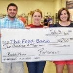 "Columbia Rotaract members Josh Beck, Jolyn Sattizahn and Kate Gruenewald present a ""check"" for $200 to the Food Bank of Central and Northeast Missouri. They also collected 18 pounds of food and volunteered 28 hours."