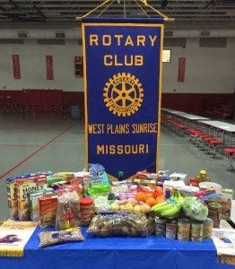 Members of the West Plains Sunrise Rotary Club display some of the 407 pounds of food they collected.