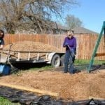 Dori Shirley, Sherry McCarthy and Bob Hansen mulch the playset area.