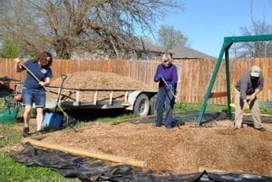 Dori Shirley, Sherry McCarthy and Bob Hansen mulch the playset area.