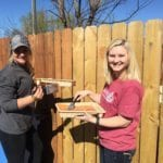 Mallory York and Baylie Borman, members of the new Rotaract club at William Woods University, stain the new gate.