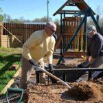 Tim Borman shovels mulch into a wheelbarrow for Bob Hansen to distribute around the playset.
