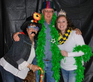 Rotarians Tammy Wickham, Henry Niles, Dori Shirley try on photo booth props during the 2016 mouse races.
