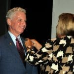 Susan Haralson pins the DG Nominee pin on Pau Reinert.